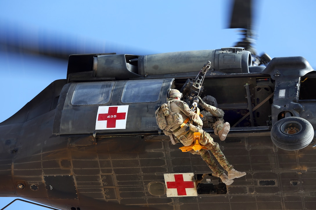 A U.S. Army UH-60 Black Hawk helicopter hoists an Australian airman on a jungle penetrator during medevac training on Multinational Base Tarin Kot in Afghanistan's Uruzgan province, Oct. 13, 2013.