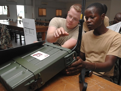"U.S. Air Force Staff Sgt. Jonathan Crouch, Operation ONWARD LIBERTY radio noncommissioned officer, helps an Armed Forces of Liberia soldier program frequencies into a CODAN 2110 Manpack Transceiver during a radio familiarization class at Camp Ware, Liberia, Sept. 11, 2013. With support from the U.S. Embassy Office of Security Cooperation, OOL mentors delivered a package of CODAN radios and provided training on the equipment to AFL communications soldiers. OOL provides mentorship to the AFL to produce a capable, respected force able to protect Liberian interests in the West African region. In addition, OOL is developing the leadership capabilities of the officers and noncommissioned officers to maintain a professional and credible military force with a reputation as a ""force for good"" among the Liberian people."