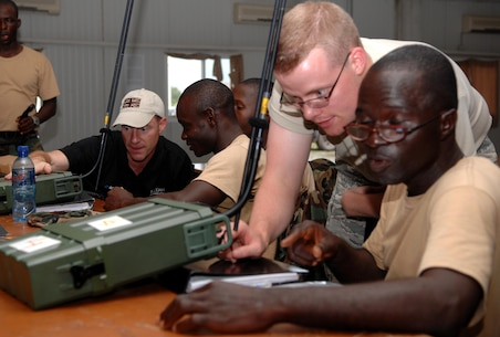 "U.S. Air Force Staff Sgt. Jonathan Crouch, Operation Onward Liberty radio noncommissioned officer, and Jon O'Keeffe, CODAN sales engineer, instruct Armed Forces of Liberia soldier as they program frequencies into a CODAN 2110 Manpack Transceiver during a radio familiarization class at Camp Ware, Liberia, Sept. 11, 2013. With the help of the U.S. Embassy Office of Security Cooperation, OOL mentors delivered a package of CODAN radios and provided training to AFL communications soldiers. OOL provides mentorship to the AFL to produce a capable, respected force able to protect Liberian interests in the West African region. In addition, OOL is developing the leadership capabilities of the officers and noncommissioned officers to maintain a professional and credible military force with a reputation as a ""force for good"" among the Liberian people."