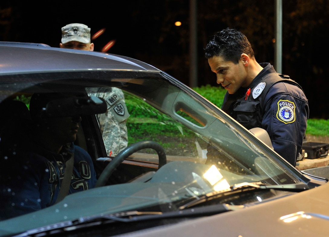 Edwin Hernandez Jr., Joint Base Elmendorf-Richardson civilian police officer, talks with a driver during Operation Nighthawk on JBER, Oct. 12. The operation was a random driving-under-the-influence checkpoint the 673d Security Forces Squadron set up to administer preliminary breathalyzer tests to all driving military members or to civilians who showed signs of being intoxicated. The purpose of the checkpoint was to deter military members from drinking and driving. (U.S. Air Force photo/Airman 1st Class Tammie Ramsouer)