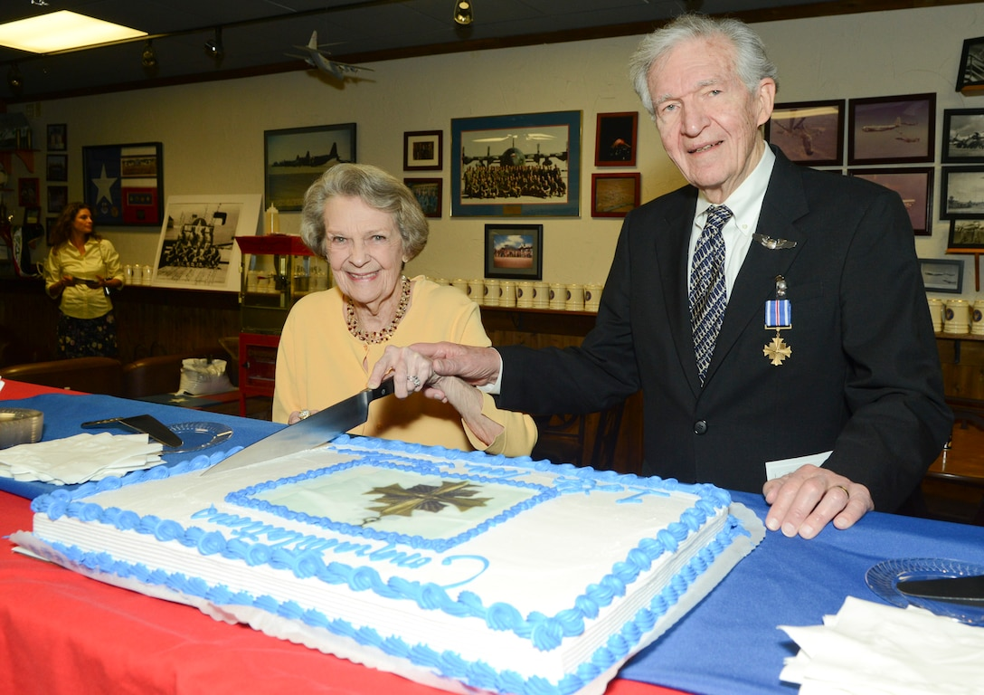 Thomas P. Faulkner, a former pilot and 1st. Lt. of the U.S. Army Air Forces' 15th Air Force, in Italy during WWII cuts the Distinguished Flying Cross cake with his wife in celebration of his award for his 28th mission at the age of 19. Faulkner, now 88 received his DFC 68 years after the fact at the 136th Airlift Wing, Naval Air Station Fort Worth Joint Reserve Base, Texas, Sept. 19, 2013. (Air National Guard photo by Senior Master Sgt. Elizabeth Gilbert/released)