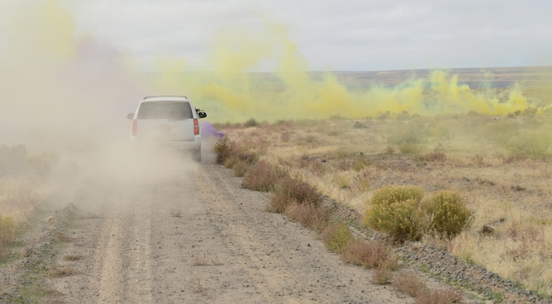 Opposition Force personnel hide inside green, yellow and purple colored smoke as Marines from 1st Air Naval Gunfire Liaison Company drive through it as part of combat search and rescue training Oct. 14, 2013, at the Saylor Creek range.  Hundreds of German Airmen and Soldiers, Royal Canadian Airmen, U.S. Marines, Sailors, Soldiers and Airmen are utilizing Mountain Home Air Force Base, Idaho, for a variety of training scenarios during Mountain Roundup 2013. (U.S. Air Force photo by Senior Airman Benjamin Sutton/RELEASED)