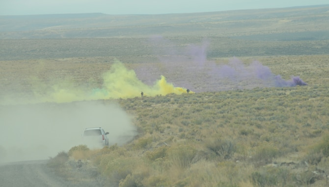 Opposition Force personnel hide inside green, yellow and purple colored smoke as Marines from 1st Air Naval Gunfire Liaison Company extract two downed German Air Force pilots as part of combat search and rescue training Oct. 14, 2013, at the Saylor Creek range. A multitude of various aircraft and servicemembers have been busy at Mountain Home Air Force Base, Idaho, since Sept. 30 during the multinational combined-joint exercise dubbed Mountain Roundup 2013. (U.S. Air Force photo by Senior Airman Benjamin Sutton/RELEASED)