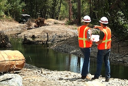 Kelly Janes, left and Zak Talbott, San Francisco District Department of the Army interns, review project plans alongside the completed Reach 15 Restoration Project at Lake Sonoma August 8.