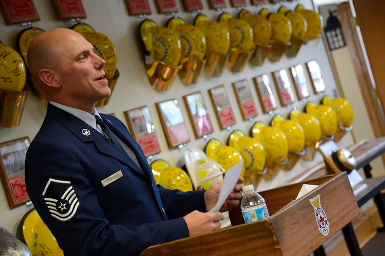 Amid a backdrop of memorial plaques and helmets honoring their members, Master Sgt. Mark Legvold, base fire chief, prepares for the closing ceremony of the 133rd Fire Department on Sept 22.  The ceremony honored firefighters from the past and present and were able to reflect not only on their heritage of service, but on the human aspect of the cuts the military has faced in 2013.  (U.S. Air National Guard photo by Tech. Sgt. Lynette Olivares/ Released)