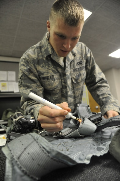 U.S. Air Force Airman 1st Class William Butler, 509th Operations Support Squadron aircrew flight equipment technician, sears frayed threads on a harness at Whiteman Air Force Base, Mo., Oct. 9, 2013. This process ensures the equipment is clean and free of any wear and tear. (U.S. Air Force photo by Airman 1st Class Keenan Berry/Released)