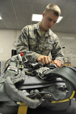 U.S. Air Force Airman 1st Class William Butler, 509th Operations Support Squadron aircrew flight equipment technician, inspects the pockets of a back automatic-22 parachute to ensure the presence of strobe lights, Whiteman Air Force Base, Mo., Oct. 9, 2013. Strobe lights are used to signal for rescue once the pilot has ejected and is awaiting extraction. (U.S. Air Force photo by Airman 1st Class Keenan Berry/Released)
