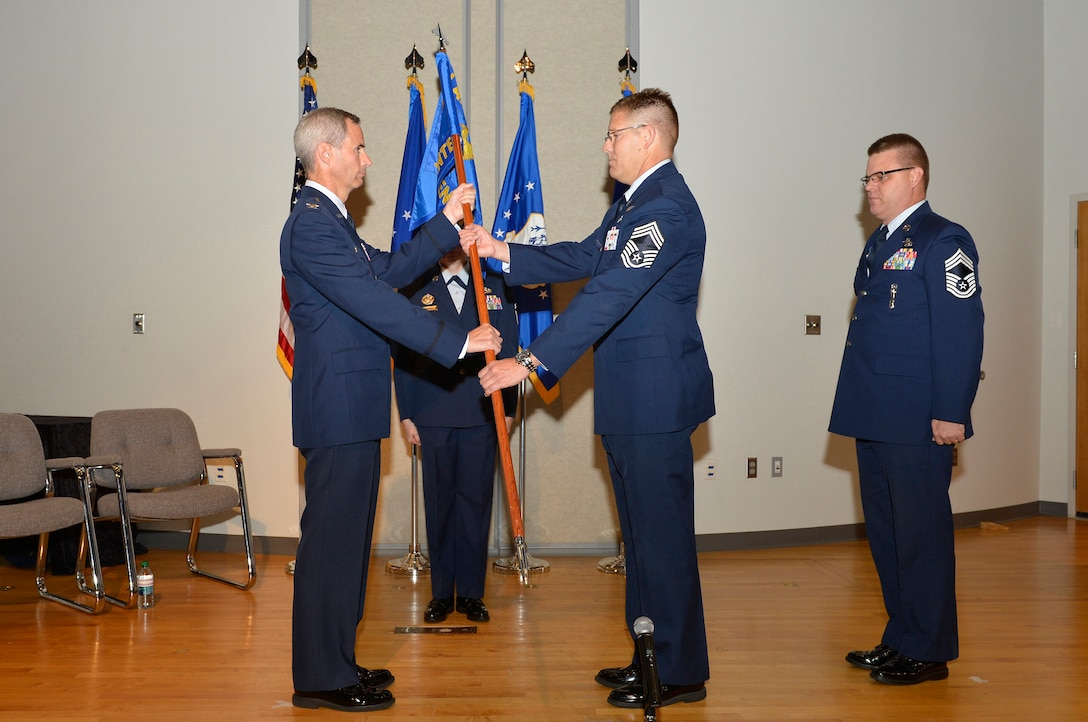 Col. Timothy Cathcart, commander of the I.G. Brown Training and Education Center (TEC), hands the guidon to Chief Master Sgt. Thomas K. Stoudt, who takes charge as the 13th commandant of the Paul H. Lankford Enlisted Professional Military Education Center here during a change of commandant ceremony Oct. 17 on the TEC campus at Spruance Hall. (U.S. Air National Guard photo by Master Sgt. Kurt Skoglund/Released)