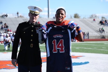 Maj. Gregory P. Gordon, the Commanding Officer of Recruiting Station St. Louis, presents a Semper Fidelis All-American Bowl jersey to high school senior Kyron Watson during a football game in East St. Louis, Ill., Oct. 19, 2013. Watson was selected to participate in the Semper Fidelis All-American Bowl in January in Carson, Calif. Watson plays Linebacker on the East St. Louis Senior High School varsity football team and is ranked a four-star recruit and 105th in the ESPN top 300. He has had 10 scholarship offers, but committed to play at the University of Kansas. (Official U.S. Marine Photo by Cpl. Erik S. Brooks Jr.)