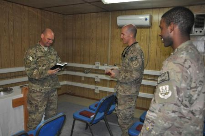 Chaplain (Maj.) Gary Coburn, 455th Air Expeditionary Wing deputy wing chaplain, speaks to Lt. Col. Daniel Hendrix, 41st Expeditionary Electronic Combat Squadron, and Senior Airman Jeremie Bumpers, 455th Expeditionary Maintenance Squadron, during a non-denominational Christian worship service at the Bagram Airfield flightline chapel Oct. 20, 2013. (U.S. Air Force photo/Tech. Sgt. Rob Hazelett)