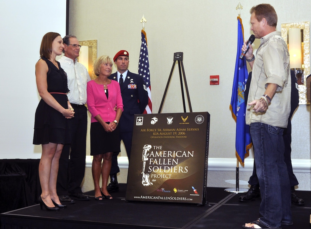 Artist Phil Taylor speaks to the family of Senior Airman Adam Servais before presenting the portrait honoring his service Oct. 19, 2013, in Destin, Fla. Servais was killed in action Aug. 19, 2006, while deployed to Afghanistan as a 23rd Special Tactics Squadron combat controller.