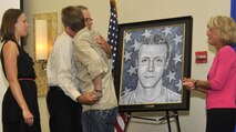 Peter Servais (left) hugs artist Phil Taylor as his daughter, Laura, and wife, Susan, look on after the unveiling of the portrait in honor of his son, Senior Airman Adam Servais Oct. 19, 2013, in Destin, Fla. Servais was killed in action Aug. 19, 2006, while deployed to Afghanistan as a 23rd Special Tactics Squadron combat controller.