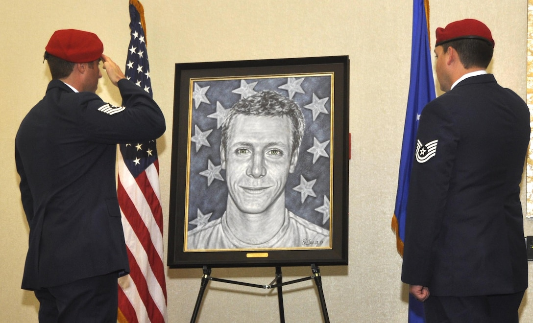 Combat controllers salute the portrait of Senior Airman Adam Servais during a presentation Oct. 19, 2013, in Destin, Fla. Servais was killed in action Aug. 19, 2006, while deployed to Afghanistan as a 23rd Special Tactics Squadron combat controller.