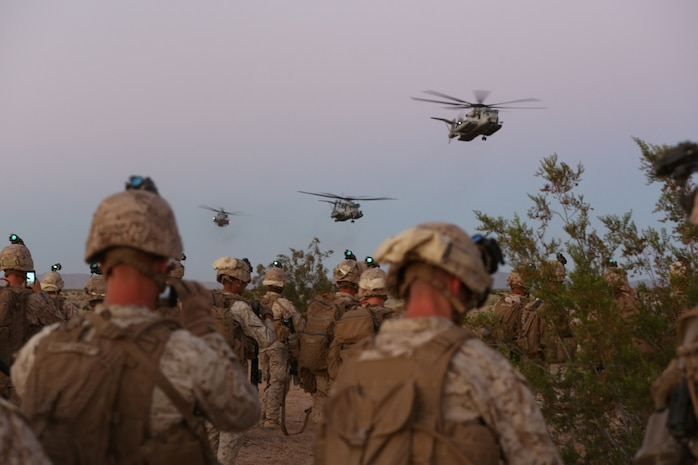 Marines with Bravo Company, 1st Battalion, 7th Marine Regiment, watch as CH-53E Super Stallion helicopters prepare to land before beginning a high value individual raid exercise here, Oct. 8, 2013. The Bravo Co. Marines inserted during night via the helicopters and patrolled to a nearby road where a Marine role playing as a suspected high-ranking insurgent traveled. Once the suspected vehicle arrived, the Marines stopped the travelers, searched and questioned each individual and searched the vehicle for weapons and other forms of intelligence. The battalion is participating in Weapons Training Instructor course before deploying to Afghanistan this spring.