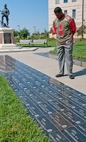 Herschel Walker, mixed martial artist and former NFL star, looks at bricks Sept. 25 bearing the names of service members who have made the ultimate sacrifice while serving with the 1st Inf. Div.  Photo by: Sgt. Michael Leverton, 1ST INF. DIV.