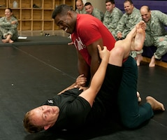 Herschel Walker, mixed martial artist, former NFL player and 1982 Heisman Trophy winner, wrestles with Sgt. Brad Cannon, Fort Riley and 1st Inf. Div. combatives NCOIC, Sept. 25, at Fort Riley.  Photo by: Sgt. Michael Leverton, 1ST INF. DIV.