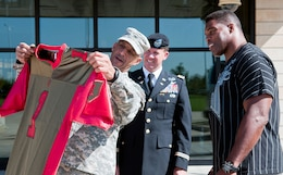 "Col. David Miller, chief of staff, 1st Inf. Div., left, and Col. John Morgan, deputy chief of staff, 1st Inf. Div., center, present Herschel Walker with a ""Big Red One"" football jersey Sept. 25 outside the division headquarters building. Building 580 was just one of Walker's stops during his visit to Fort Riley to meet with fans and talk about his struggles with mental health.  Photo by: Sgt. Michael Leverton, 1ST INF. DIV."