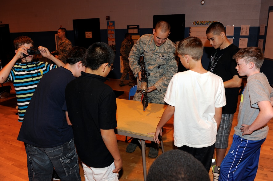 Staff Sgt. Joseph Glover, 49th Security Forces Squadron, displays various tactical devices to students during Holloman Middle School's Science Discovery Night at Holloman Air Force Base, N.M., Oct. 18. Students of HMS, as well as various base organizations, displayed projects for all to see. (U.S. Air Force photo by Master Sgt. Kevin P. Milliken/Released)