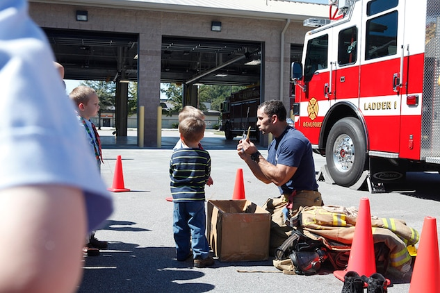 Students play a game with fire fighter, Bobby Clark, during a visit to the Air Station Structural Fire Department, Oct. 11.