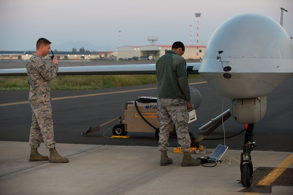 Airmen attached to the 324th Expeditionary Reconnaissance Squadron perform a preflight inspection on an MQ-1 Predator unmanned aerial vehicle Oct. 22, 2013. (U.S. Navy photo/Mass Communication Specialist 2nd Class Brian T. Glunt)