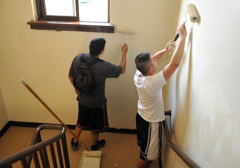 "Airmen 1st Class Rod Galvan, left, 51st Security Forces Squadron force protection member, and Fausto Lopez, 51st SFS entry controller, re-paint a stairwell in Bldg. 1436 during a ""Worst Dorm First"" renovation at Osan Air Base, Republic of Korea, Oct. 23, 2013. Ninety dorm residents and 15 members of the 51st Civil Engineer Squadron Structures Shop re-painted the entire interior of the building, refurbished the day rooms, and built a patio and a volleyball court for the dorm. (U.S. Air Force photo/Airman 1st Class Ashley J. Thum)"