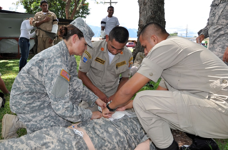 U.S. Army Specialist Lourdes Tarin, an emergency medical technician assigned to Joint Task Force-Bravo, instructs Honduran firefighters on the proper care for a victim as part of a basic life support class conducted at Soto Cano Air Base, Honduras, Oct. 23, 2013.  Members of Joint Task Force-Bravo's Medical Element (MEDEL) trained 19 local firefighters in basic life support skills.  (U.S. Air Force photo by Capt. Zach Anderson)