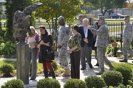 Col. John M. Devillier, Air Force Mortuary Affairs Operations commander, highlights the Angel and the Dying Unknown sculpture outside the Center for Families of the Fallen, Dover Air Force Base, Del., during an open house the mortuary hosted Oct. 22, 2013 for Team Dover. (U.S. Air Force photo/Senior Airman Laura Beckley)