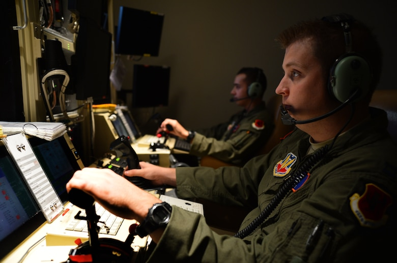 Capt. Ben (front), 432nd Wing/432nd Air Expeditionary Wing Remotely Piloted Aircraft pilot, and Senior Airman Travis, 432nd Wing/432nd AEW RPA sensor operator, fly an MQ-1 Predator during the wing's 2 million flying hour milestone Oct. 22, 2013.  The wing flew its first 1 million hours in April 2011. The wing's 2 million hour mark was achieved 32 months later, culminating in more than 215,000 total missions completed and nearly 94 percent of all missions flown in support of major combat operations due in large part to total force integration efforts and an expansion of combat air patrols. (U.S. Air Force photo by Staff Sgt. N.B./released)