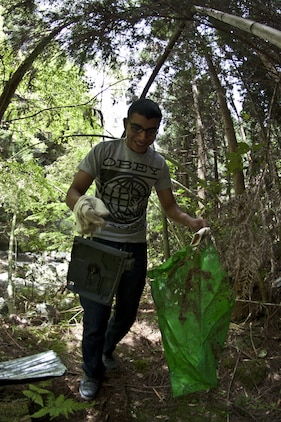 "A Single Marine Program cleanup event participant picks up trash while walking through one of the trails at Futashika Umezu Falls and park, May 17, 2013. ""I like to volunteer to a cause,""said Maria Molinalemus, SMP river cleanup participant. ""If you can't give out money, then you have to give a piece of yourself and I think helping out the community is the best thing. ... It's about helping out."""