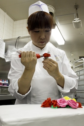 Kaori Nohara, a Club Iwakuni chef, uses a piping bag to make roses to decorate a birthday cake for a customer at Club Iwakuni, Marine Corps Air Station Iwakuni, Japan, June 21, 2013. Nohara has been baking for nearly eight of the 13 years she has worked at the club.