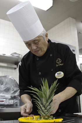 Senji Shoya, Club Iwakuni supervisor, prepares a fruit display for an upcoming party at Club Iwakuni at Marine Corps Air Station Iwakuni, Japan, June 27, 2013. Shoya is in charge of planning large events, including the Marine Corps Birthday Ball.