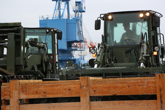 A Marine with Marine Wing Support Squadron 171, Marine Aircraft Group 12, drives a forklift carrying a crate full of equipment to a staging area where it is loaded onto a cargo ship bound for Tinian for Exercise Forager Fury II, at the Marine Corps Air Station Iwakuni, Japan, harbor, Oct. 23, 2013. The ship's cargo includes more than 200 units of equipment including vehicles for the exercise.
