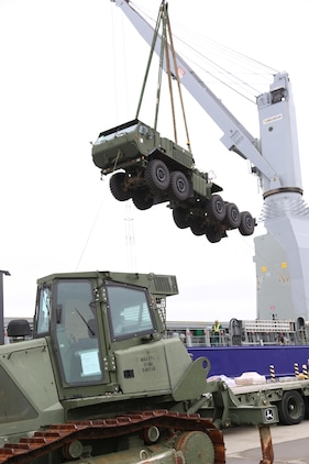 A crane lifts a Logistics Vehicle System Replacement Cargo Vehicle (LVSR) into the air to load onto a cargo ship bound for Tinian for Exercise Forager Fury II, at the Marine Corps Air Station Iwakuni, Japan, harbor, Oct. 23, 2013. The vessel is a 'lift on lift off' ship, meaning a crane must lift each piece of equipment on and off the ship.