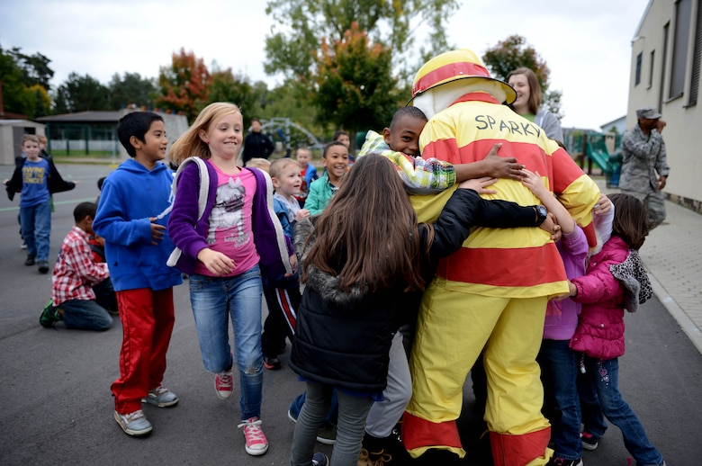 Children rush to meet Sparky the Fire Dog as part of Fire Prevention Week Oct. 9, 2013, at Spangdahlem Air Base, Germany. Sparky and his firefighting companions reminded children to be safe and that firefighters are their friends. (U.S. Air Force photo/Airman 1st Class Kyle Gese)