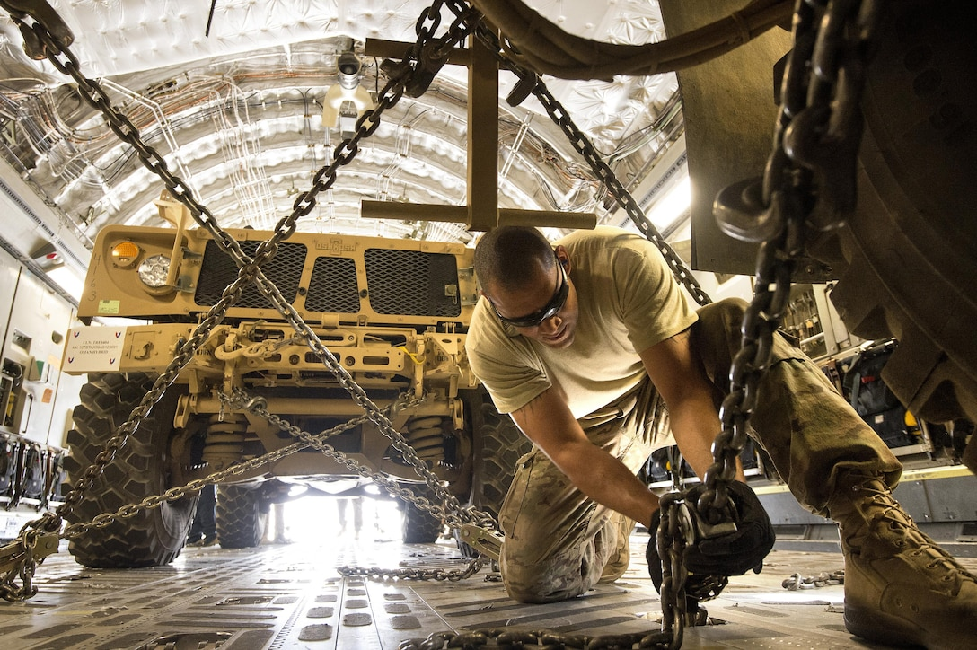 Staff Sgt. Ryan Vanterpool chains down a mine-resistant, armored-protective vehicle, known as an MRAP, on a C-17A Globemaster III Oct. 2, 2013, at Bagram Airfield, Afghanistan. Bagram has become a major hub for retrograde operations out of Afghanistan. The 455th Expeditionary Aerial Port Squadron special handling section pushed 4.2 million pounds of retrograde equipment during the month of September. Vanterpool, a Honolulu, Hawaii native, is deployed from Joint Base McGuire-Dix-Lakehurst, N.J. Vanterpool is a 455th EAPS aerial porter. (U.S. Air Force photo/Master Sgt. Ben Bloker)