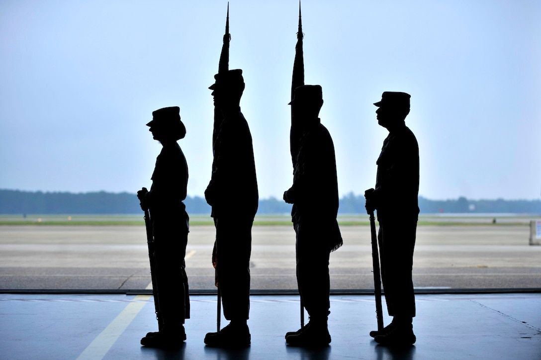 Members of the Shaw Air Force Base Honor Guard stand at attention in preparation to present the colors during a retirement ceremony Oct. 18, 2013, at Shaw AFB, S.C. Shaw's honor guard pride themselves on working together as a cohesive unit while performing their duties at each ceremony they attend. (U.S. Air Force photo/Airman 1st Class Jensen Stidham)