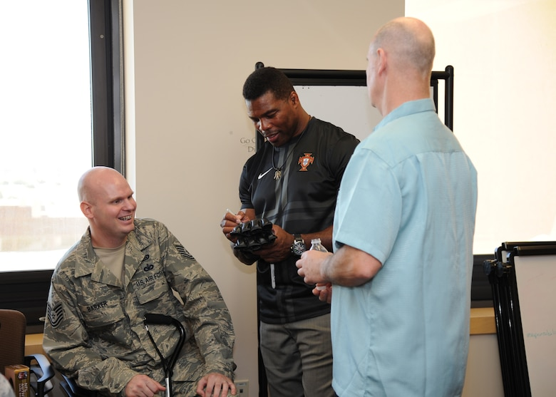 Herschel Walker, center, signs an autograph for Tech. Sgt. Christopher Barker and his father Daniel Barker Oct. 23, 2013, during a recent visit to the Wilford Hall Ambulatory Surgical Center Oct. 23, 2013, at Joint Base San Antonio-Lackland, Texas. Earlier in the day, Barker was presented with the distinguished Purple Heart for wounds sustained in action. Barker is a member of the 59th Medical Wing Patient Squadron.