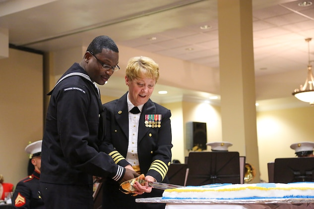 Navy Capt. Anne Lear, the commanding officer for Naval Hospital Beaufort, and Seaman Shaquille Lewis, a corpsman with 3rd Battalion Aid Station aboard Marine Corps Recruit Depot Parris Island, share the honor of making the first cut to the birthday cake during the Navy Ball at the Holiday Inn in Beaufort, S.C., Oct.19. It is tradition for the youngest and oldest sailor to cut the cake signifying the passing of traditions from one generation of sailors to another.