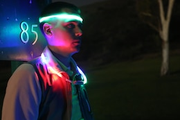 Cpl. Jordan Barker waits for his turn to tee off during the Glow-Ball tournament at the Marine Memorial Golf Course on base Oct. 25.The par three course was nine holes, dimly lit by neon lights at each hole and the lighted necklaces the participants wore. Barker is an Arabic cryptologic linguist with 1st Radio Battalion, 1st Marine Expeditionary Force.
