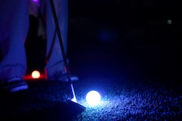 Lance Cpl. Travis Wendt lines up his wedge during the Glow-Ball tournament at the Marine Memorial Golf Course Oct. 25. The par three course was nine holes, dimly lit by neon lights at each hole and the lighted necklaces the participants wore. Wendt is a middle-eastern cryptologic linguist with 1st Radio Battalion, 1st Marine Expeditionary Force.