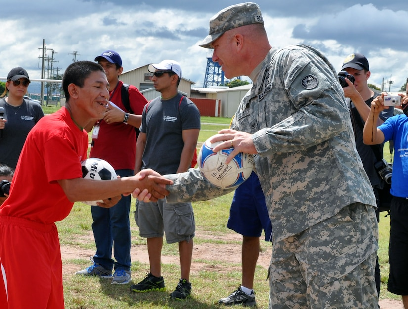 "U.S. Army Col. Thomas Boccardi, Joint Task Force-Bravo commander, presents soccer balls to participants of the Honduras Special Olympics soccer tournament at Soto Cano Air Base, Honduras, Oct. 25, 2013.  Boccardi presented the balls as part of ""Kick for Nick,"" a non-profit organization founded in honor of U.S. Army Pvt. Nick Madaras. While serving in Iraq in 2006, Madaras gathered soccer balls to give to underprivileged children near his post. However, he was killed and was never able to distribute the balls himself. Shortly after his death, the ""Kick for Nick"" organization was established in his honor. Today, soccer balls are donated and distributed to underprivileged children around the world through ""Kick for Nick,"" in memory of Pvt. Madaras. (U.S. Air Force photo by Capt. Zach Anderson)"