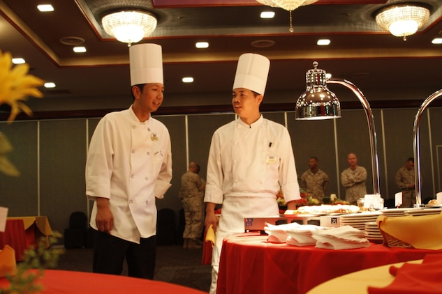 Mori Nobu, left, Club Iwakuni sous chef, walks with another chef as they check food preparation before serving it at a reception for Col. James C. Stewart, former station commanding officer, in the Club Iwakuni ballroom at Marine Corps Air Station Iwakuni, Japan, July 12, 2013. Nobu has 13 years of experience at Club Iwakuni and is second-in-command of the kitchen.