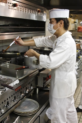 Yasunobu Asaeda, Club Iwakuni supervisor, prepares chicken stir-fry while the other chefs complete orders for a busy breakfast rush at Club Iwakuni at Marine Corps Air Station Iwakuni, Japan, July 20, 2013. When chefs need an extra hand completing orders, Asaeda steps in to assist making dishes.