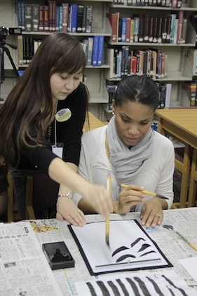 Nami Yamamoto, Youth Cultural Program coordinator, helps a student practice her calligraphy writing techniques at New Year New Hobby's calligraphy night held at the library in Building 411, Jan. 10, 2013. Other classes taught students about playing card games, scrapbooking and making Origami figures. The program's goal is to help introduce people to something new.