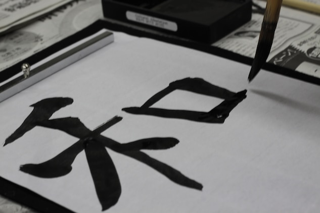 "A student participating in the New Year New Hobby program practices writing the Kanji ""Wa,"" which stands for harmony, at calligraphy night at the library in Building 411, Jan. 10, 2013. The class consisted of proper brush holding technique, how to execute strokes, and the history behind calligraphy."