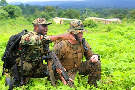 A Cameroonian soldier relays his troops' situation to 1st Lt. Logan Brewer, a U.S. Marine advisor assigned to Africa Partnership Station 13, during a simulated raid on their objective as part of their final exercise. The military-to-military engagement in Limbe, Cameroon, from October 18-25 was the last stop on APS' three-month tour around the west coast of Africa aboard the HNLMS Rotterdam (L800), a Royal Netherlands Navy (RNLN) landing platform dock, that conducted training engagements with African nations to increase maritime security, partner-nation military capacity, and promote regional stability.