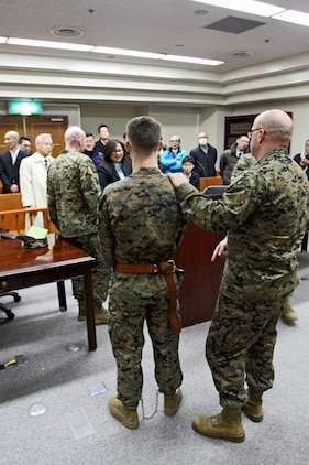 Master Sgt. Wade Campbell, (Right) pre-trial facilities officer-in-charge, and Lance Cpl. Frank Pikula, (Left) legal services clerk, demonstrate restraint equipment used to subdue hostile defendants awaiting trial in the pre-trial facility of the Station Judge Advocates courtroom here, Feb. 7, 2013, during an outreach program offered to Hatsukaichi police inspectors.