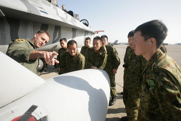 Capt. Sean Roberts, a FA-18/D Hornet pilot with Marine All Weather Fighter Attack Squadron 224, points out different parts of a FA-18/D to members of the Japan Ground Self Defense Force during a recent visit to Marine Corps Air Station Iwakuni, Japan, Feb. 28, 2013. The JGSDF soldiers visited MCAS Iwakuni to learn more about the Marine Corps lifestyle and to improve on their English-speaking skills. This visit was a follow up to the yearly JGSDF English Seminar.