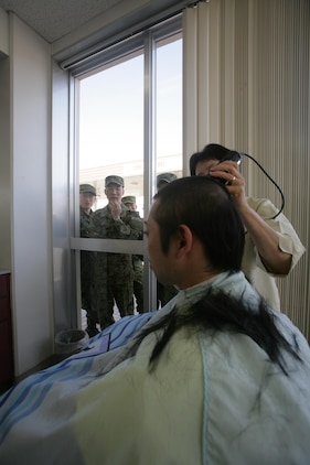 A Japan Ground Self Defense Force soldier receives a haircut at the northside barbershop during a recent visit to Marine Corps Air Station Iwakuni, Japan, Feb. 28, 2013. Two JGSDF soldiers opted to get an authentic Marine Corps haircut, a high and tight, during the three-day visit.