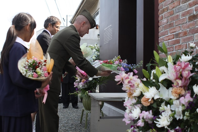 Marine Corps Air Station Iwakuni Commanding Officer Col. James C. Stewart, British consulate general of Osaka Consul-General Simon Fisher, and Mukaishima Chuo Elementary School first grader Aoi Ode, lay bouquets of flowers April 15, 2013, at the memorial site for POWs who were captured or killed at the former Mukaishima POW Sub-Camp No. 4. The part of Onomichi where the memorial stands was once known as Mukaishima, and it is here where more than 200 Allied servicemembers toiled in shipyards carrying materials until the war's end in 1945.